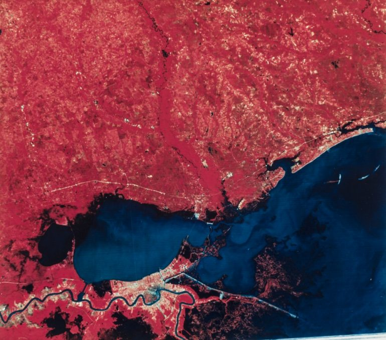 An aerial photograph shows New Orleans and the Northshore following the opening of the Bonnet Carré Spillway. Land is represented in red and water is represented in blue.