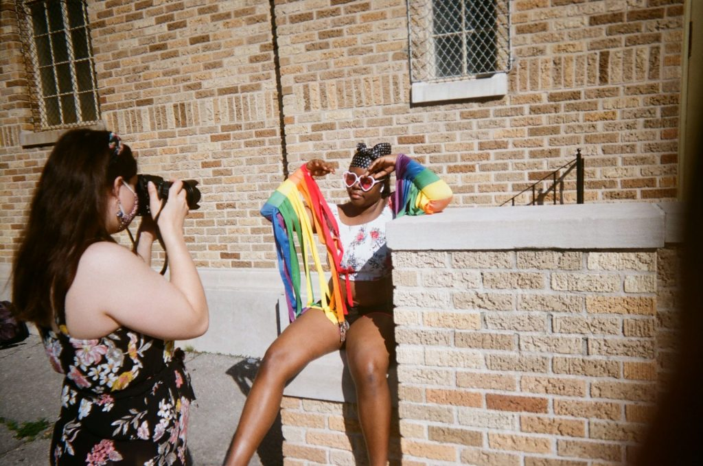 A photographer takes an image of a person sitting on a stoop wearing heart-shaped sunglasses and rainbow-colored sleeves.