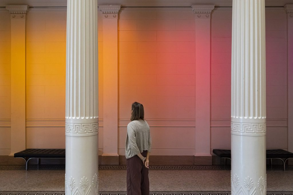 A person stands in the museum Great Hall listening to an audio installation