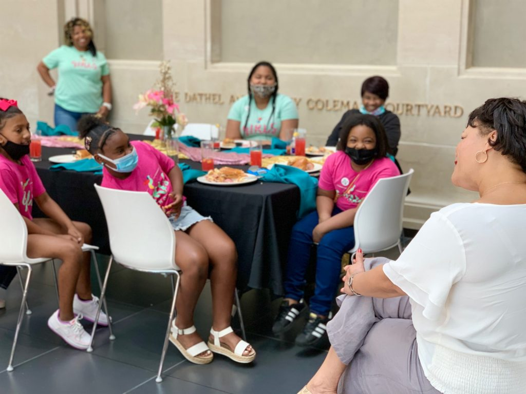 Youth in pink and blue t-shirts sit around a table and talk with New Orleans mayor LaToya Cantrell