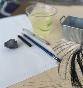 A disposable class filled with white wine sits on a table with drawing materials