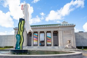 The Neoclassical façade of the New Orleans Museum of Art is visible behind an abstract sculpture by Roy Lichtenstein